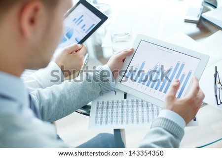 Close-up of business people working with touchpads - stock photo