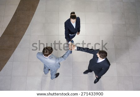 Close up of business peoples hands on top of each other - stock photo
