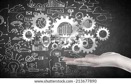 Close up of business person hand holding gears - stock photo