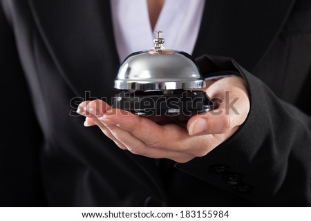 Close-up Of Business Person Holding Service Bell - stock photo