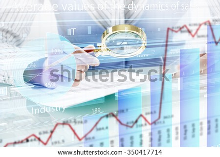 Close up of business person investigating infographs with magnifier - stock photo