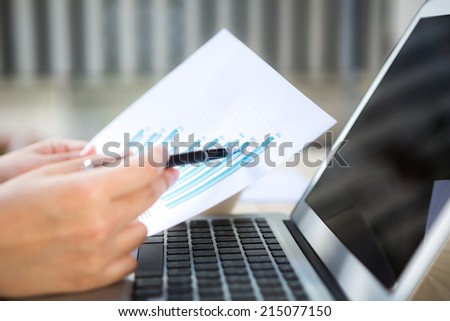Close-up of business person use laptop with financial diagram - stock photo