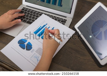 Close-up of business person using digital tablet and laptop with financial diagram - stock photo