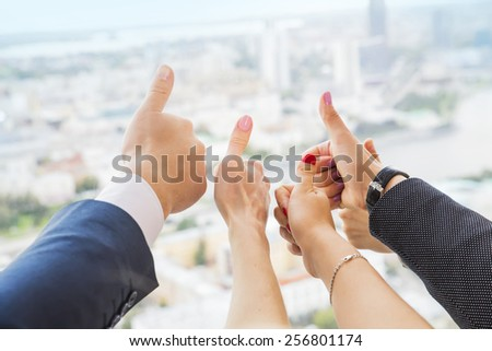 Close-up of business team holding their thumbs up against the background of the city  - stock photo