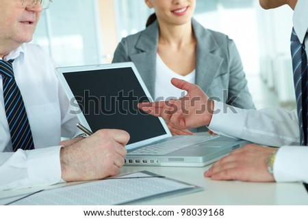 Close-up of business team of three sitting at table and planning work - stock photo