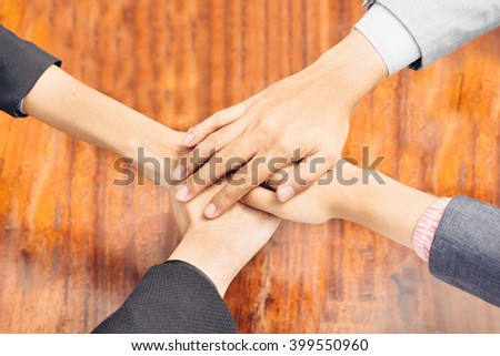 close up of business team showing unity with their hands together - stock photo