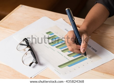 close up of business woman hand working on laptop computer with business graph information diagram on office desk  - stock photo