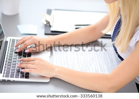 Close up of business woman hands typing on laptop computer, blue tie with polka dots