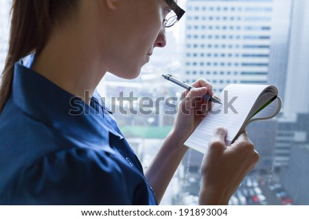 Close up of business woman writing something on the paper.  - stock photo