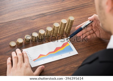 Close-up Of Businessman Analyzing Financial Graph In Front Of Stacked Coins - stock photo