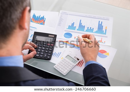 Close-up Of Businessman Analyzing Graph And Using Calculator - stock photo