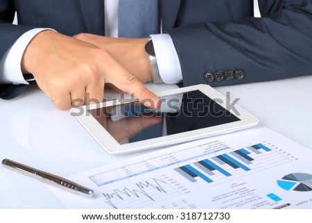 Close-up Of Businessman Analyzing Graph On Digital Tablet
