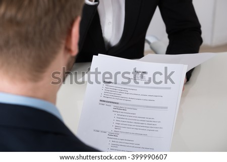 Close-up Of Businessman Analyzing Resume At Desk In Office