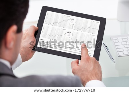 Close-up Of Businessman Analyzing Stock Market Status On Digital Tablet - stock photo