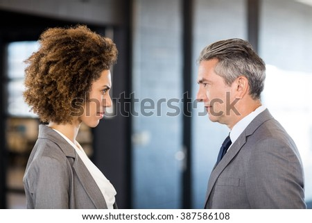 Close-up of businessman and businesswoman standing face to face in office - stock photo