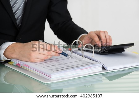 Close-up Of Businessman Calculating Bill In Office