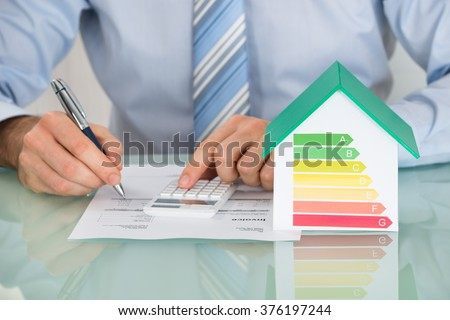 Close-up Of Businessman Calculating Energy Efficiency Rate Of House In Office - stock photo