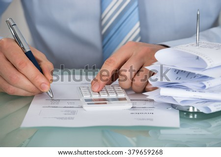 Close-up Of Businessman Calculating Invoice In Office - stock photo