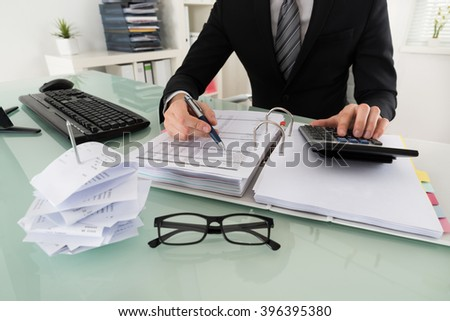 Close-up Of Businessman Calculating Tax In Office - stock photo