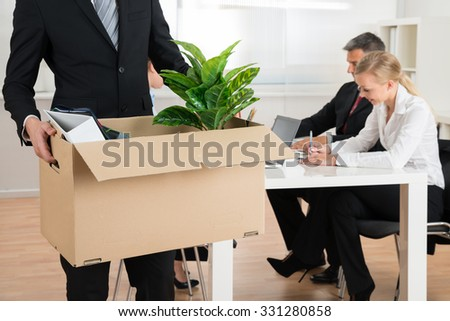 Close-up Of Businessman Carrying Personal Belongings In Office - stock photo