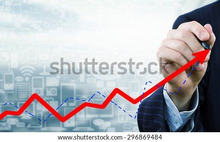 Close up of businessman drawing increasing graph with marker on media screen - stock photo