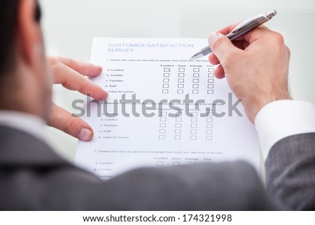 Close-up Of Businessman Filling Customer Survey Form - stock photo