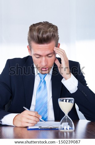 Close-up Of Businessman Filling Form With Hourglass On Desk