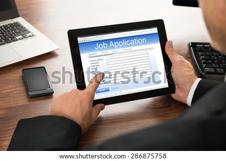 Close-up Of Businessman Filling Online Job Application On Digital Tablet - stock photo