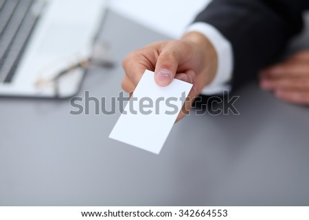 Close-up of  businessman giving a business card, sitting at the table