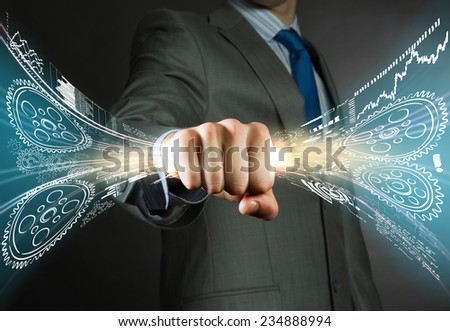 Close up of businessman grasping cogwheels in fist