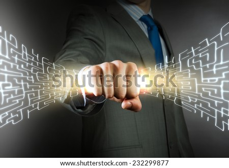 Close up of businessman grasping labyrinth in fist
