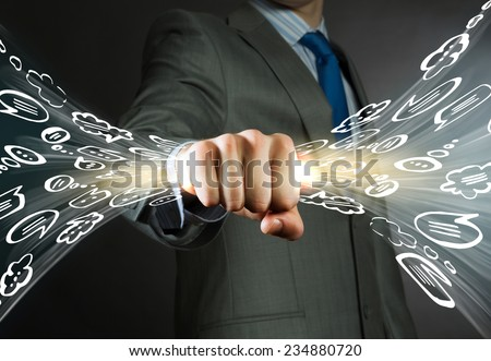 Close up of businessman grasping light in fist - stock photo