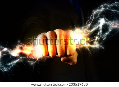 Close up of businessman grasping lightning in hand - stock photo