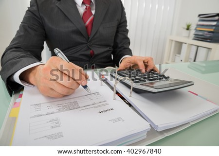 Close-up Of Businessman Hand Calculating Invoice Using Calculator At Desk In Office - stock photo