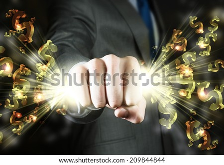 Close up of businessman hand clenching dollar signs in fist - stock photo
