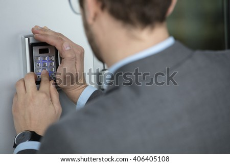 Close up of businessman hand entering pressing button on security system - stock photo