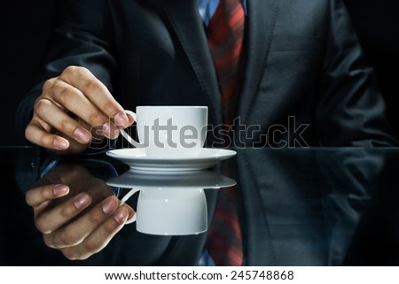 Close up of businessman hand having a cup of coffee - stock photo