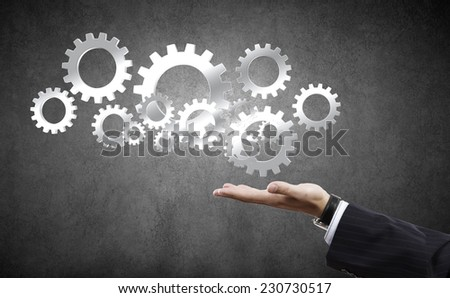 Close up of businessman hand holding gears in palm