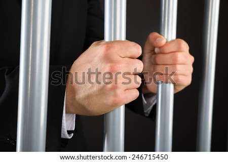 Close-up Of Businessman Hand Holding Metal Bars In Jail - stock photo
