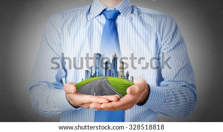 Close up of businessman hand holding modern city model