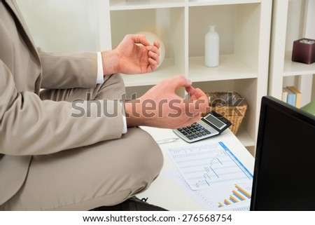 Close-up Of Businessman Hand Meditating In Lotus Position At Workplace - stock photo