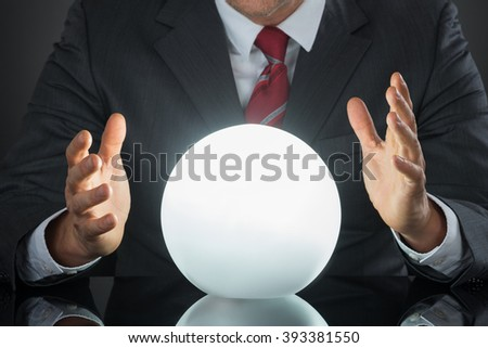 Close-up Of Businessman Hand On Crystal Ball On Desk - stock photo