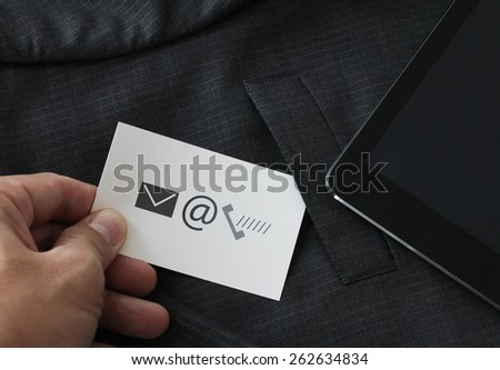 close up of businessman hand picking business card icon contact us concept from the pocket of gray suit jacket background - stock photo