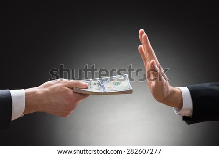 Close-up Of Businessman Hand Rejecting The Money Offered By Other Businessman