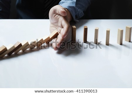 Close up of businessman hand stop dominoes continuous toppled.