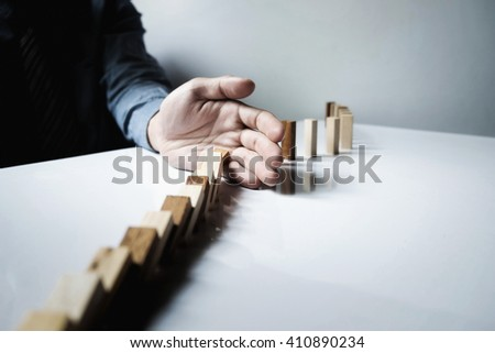 Close up of businessman hand stop dominoes continuous toppled vintage tone.
