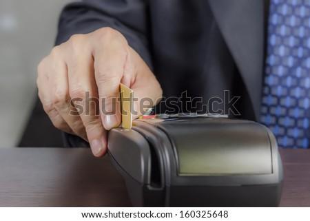Close up of businessman hand using credit card machine - stock photo