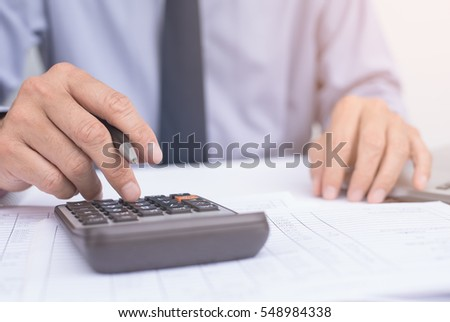 Close up of businessman hand working on accountancy document and calculator with laptop computer
