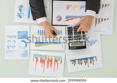 Close-up Of Businessman Hand Working On Calculator For Analyzing Graph On Desk - stock photo