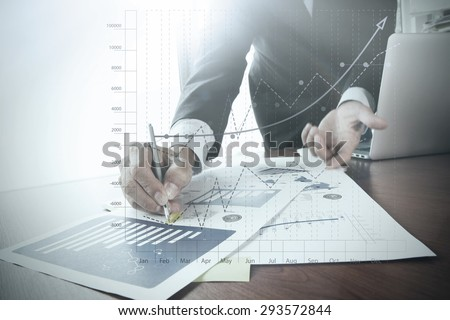 close up of businessman hand working on laptop computer with business graph information diagram on wooden desk as concept  - stock photo